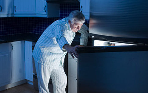 Senior man looking in refrigerator at night   Original Filename: 73032480.jpg